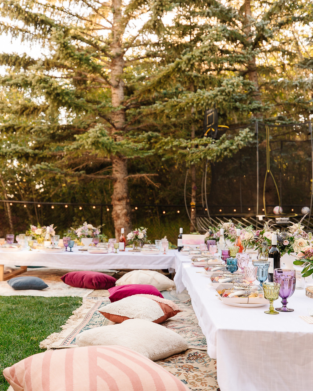 An evening backyard boho garden party with gorgeous flowers, throw pillows, vintage rugs, charcuterie wine, twinkle lights, coloured glasses, boho decor and all your best girlfriends.