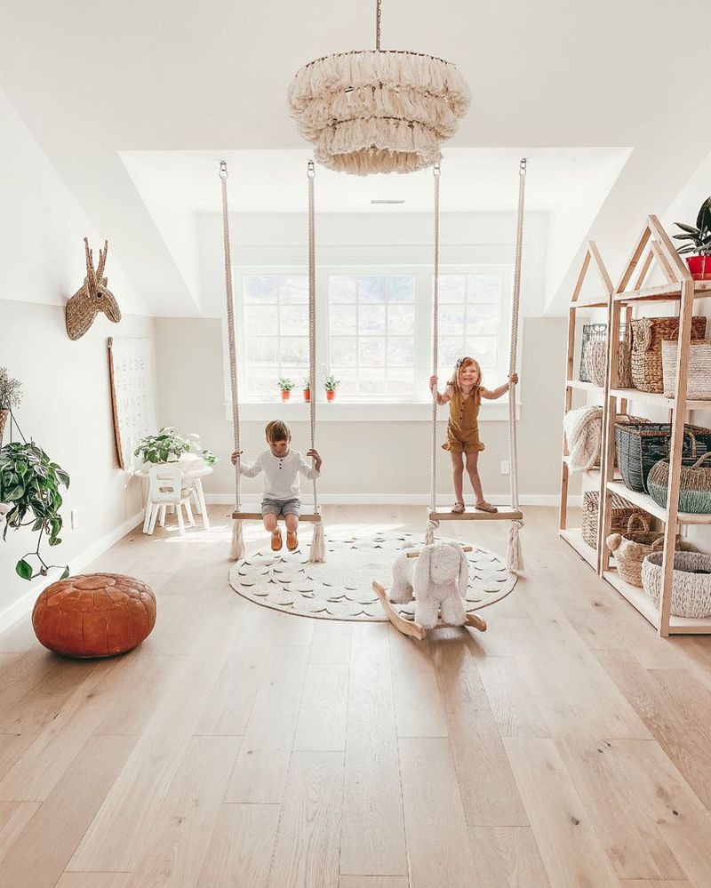 A neutral childrens playroom styled with rope style swings, white table and chairs and simple shelving with storage baskets