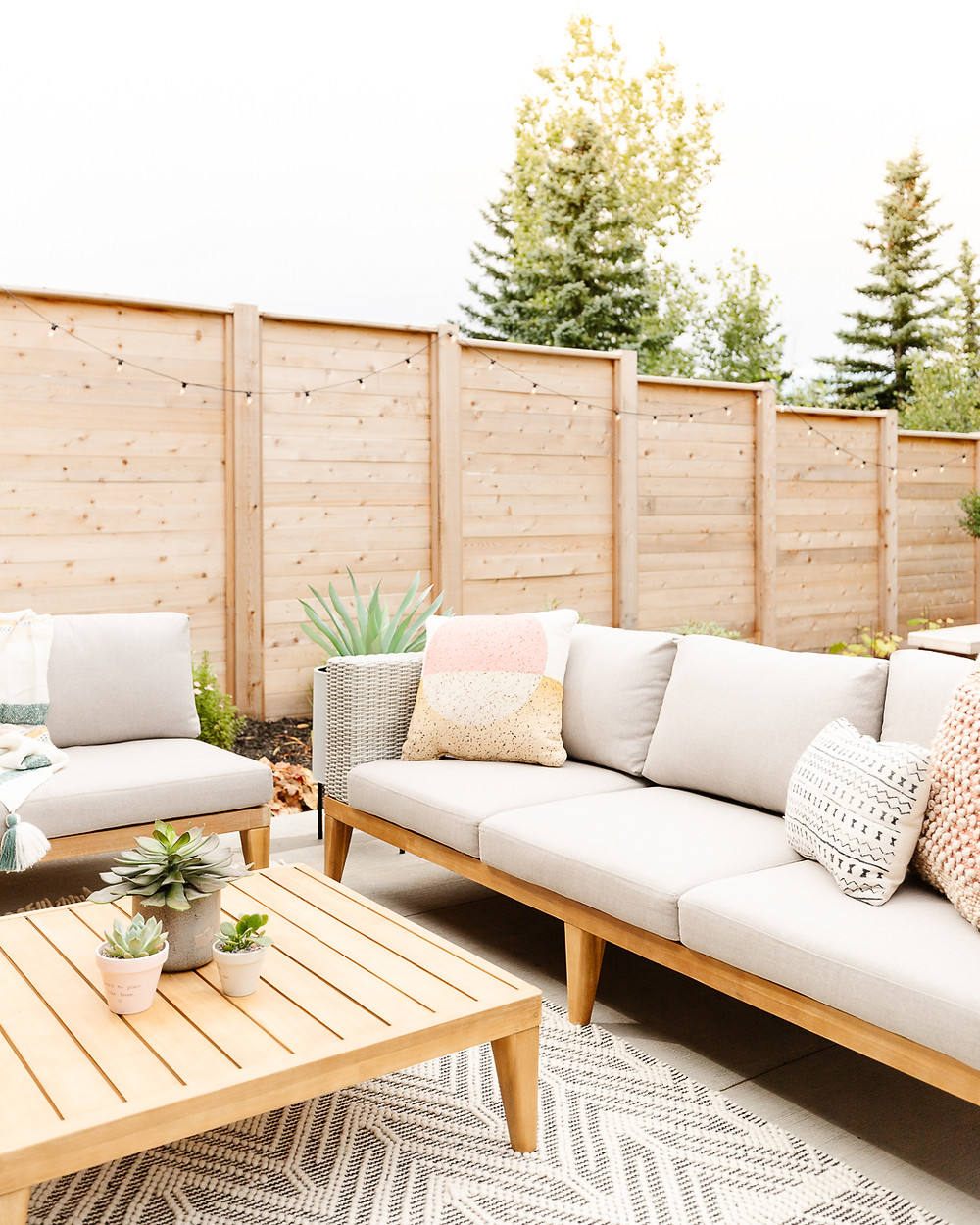 Wicker sofa with wood accents and beige cushions black and white area rug chair with wood accent and striped throw blanket wood accent table with succulent pots potted succulent plant on black stand wood fence backyard concrete patio space string lights perennial flower bed