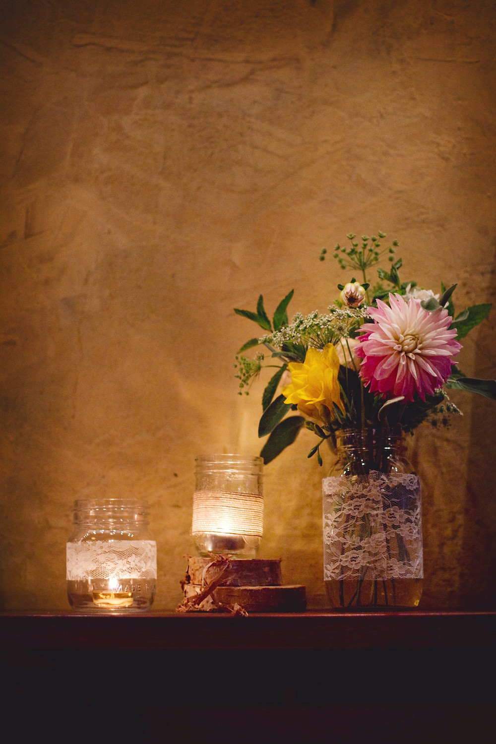Lace wrapped mason jars on top of wooden rounds old a beautiful garden bouquet on top of a wooden shelf in a rustic Italian restaurant.