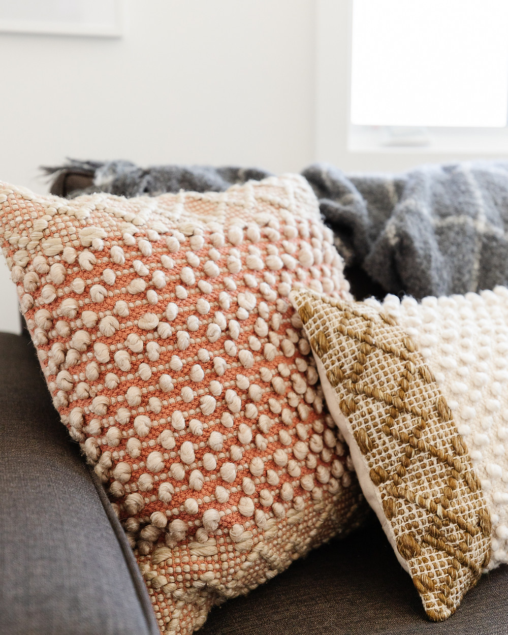 textured accent throw pillows in rust and gold on grey sofa