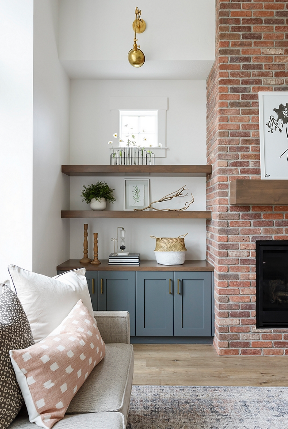 A modern living room with open wood shelves next to a brick fireplace and dusty blue grey cabinets styled with a basket, a plant, art and books.