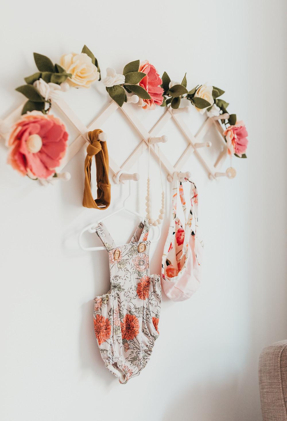 A felt floral garland hanging off an accordian rack in a nursery.