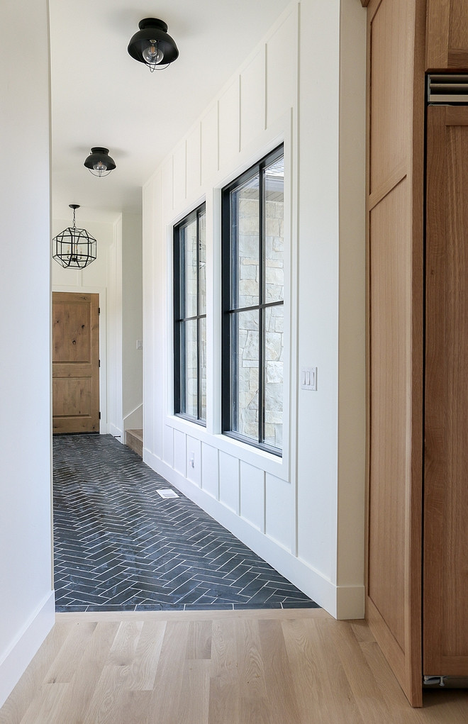 light hardwood floors black herringbone tile hallway black framed windows shiplap wall accent black industrial light fixtures hanging black pendant lantern