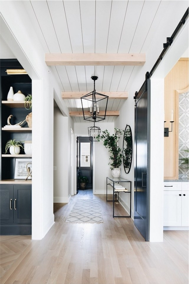barn door shiplap ceiling wood beams hallway dark cabinets black lantern pendant lights hallway runner console table with mirror