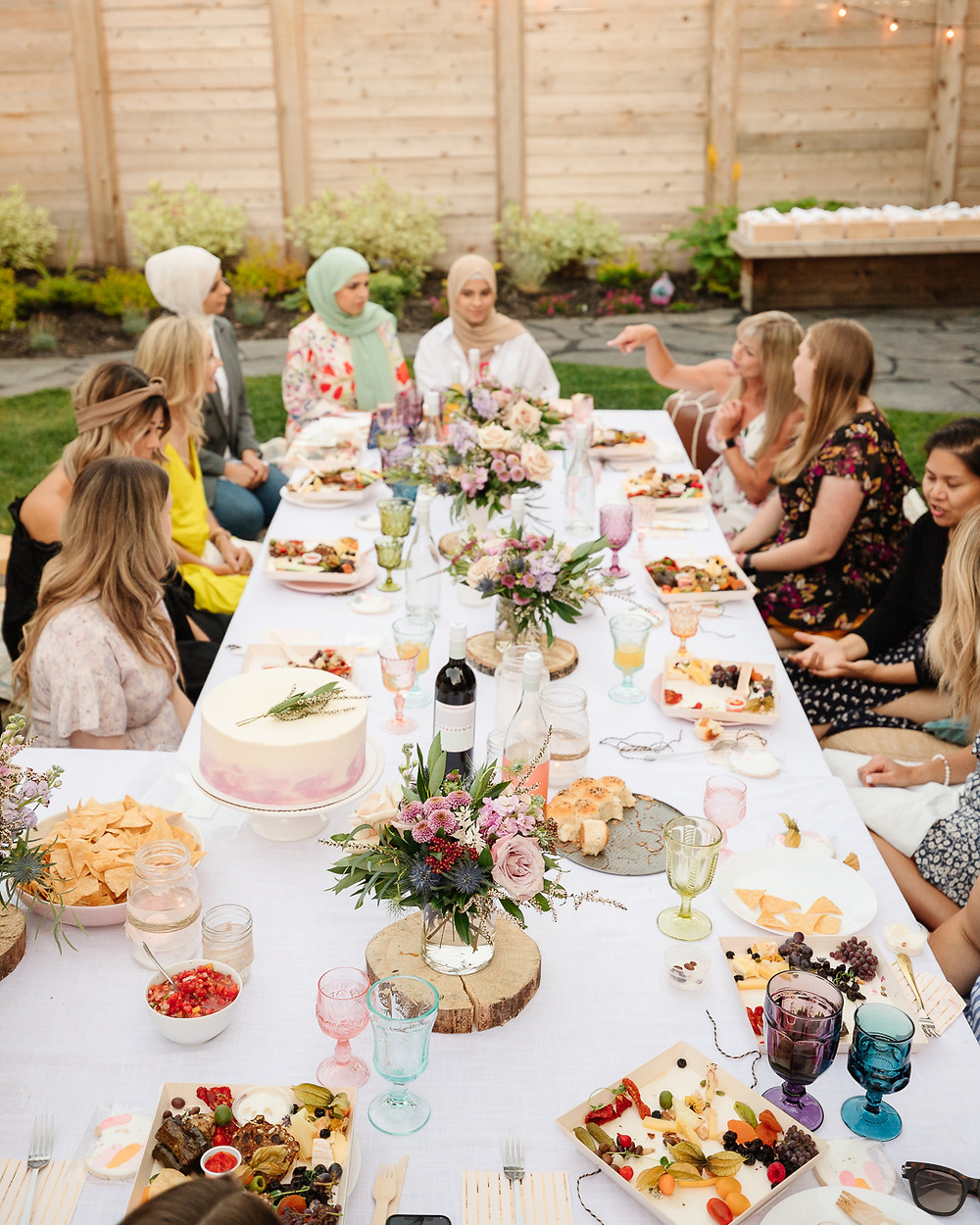 An evening backyard boho garden party with gorgeous flowers, vintage rugs, charcuterie wine, twinkle lights, coloured glasses, boho decor and all your best girlfriends.