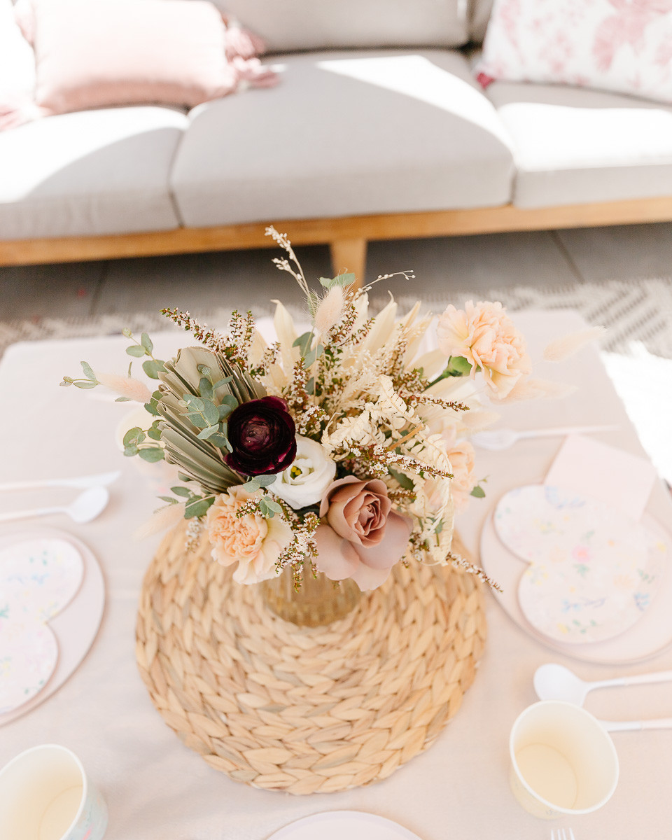 A boho bouquet of flowers and palm leaves sitting on a wicker place mat at a birthday party.
