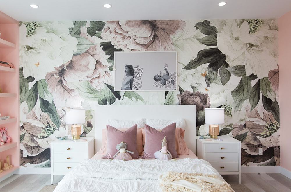 A floral wall behind a white bed and bed side tables with purple pillows.