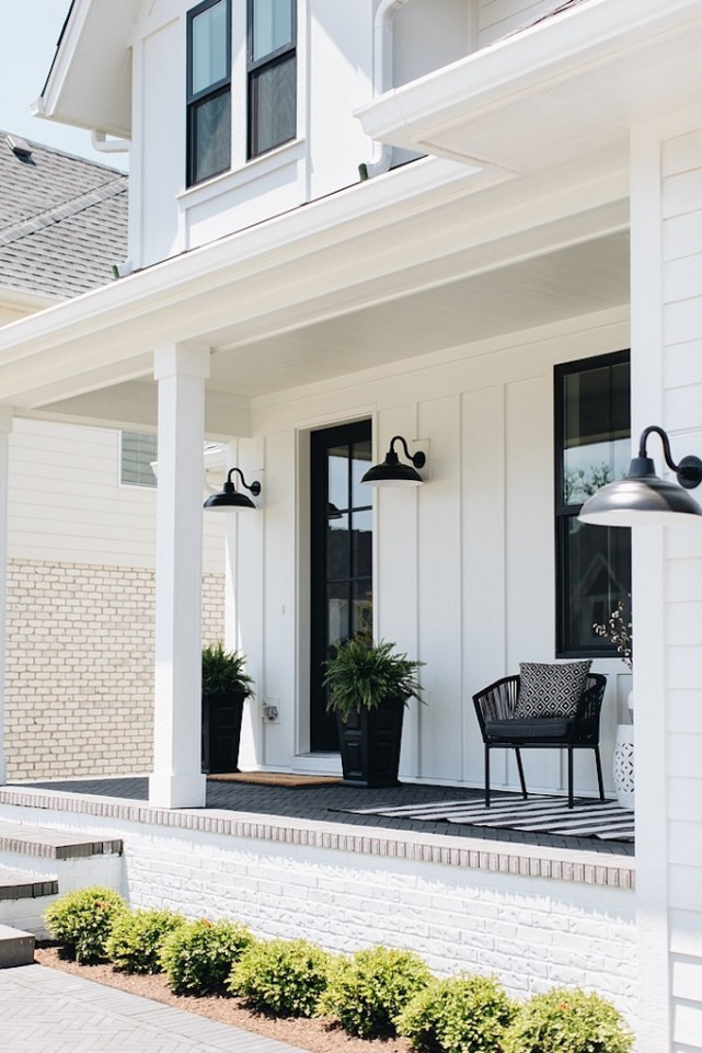 white board and batten exterior with wrap around porch black windows black gooseneck exterior lights wicker chair with black and white rug pots with plants at doorway boxwood in flower bed