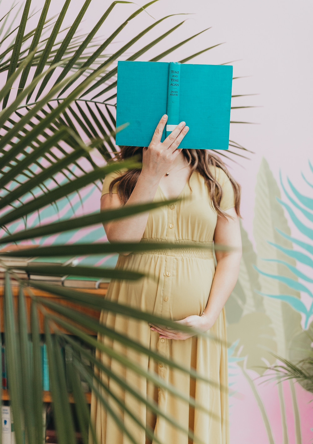 A pregnant girl holding her belly and ready a book.