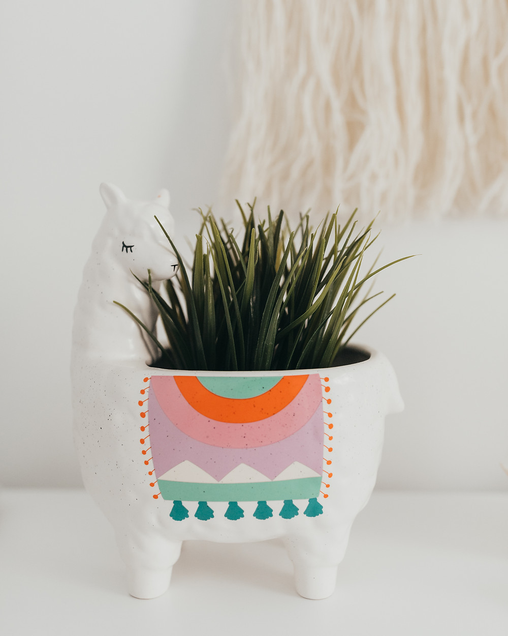 A llama plant pot with green grasses in it.