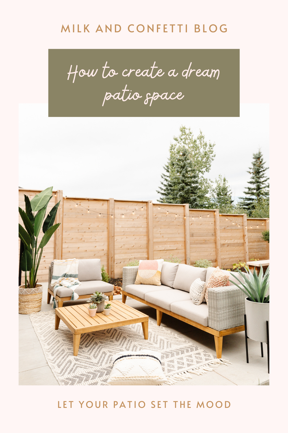 Modern outdoor patio wood fence with string lights neutral wicker sofa wood legs with beige fabric patterned throw cushions beige and black area rug teak coffee table with succulent pots black metal pot stand with aloe plant chair with striped throw blanket