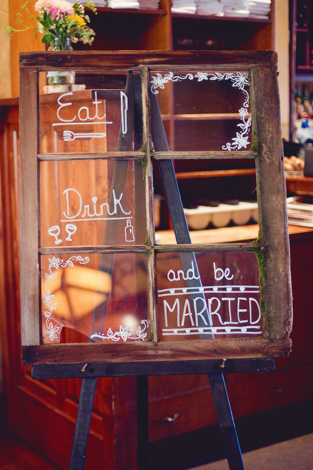 A rustic barn window displayed at a rustic Italian inspired wedding with white calligraphy writing on it.