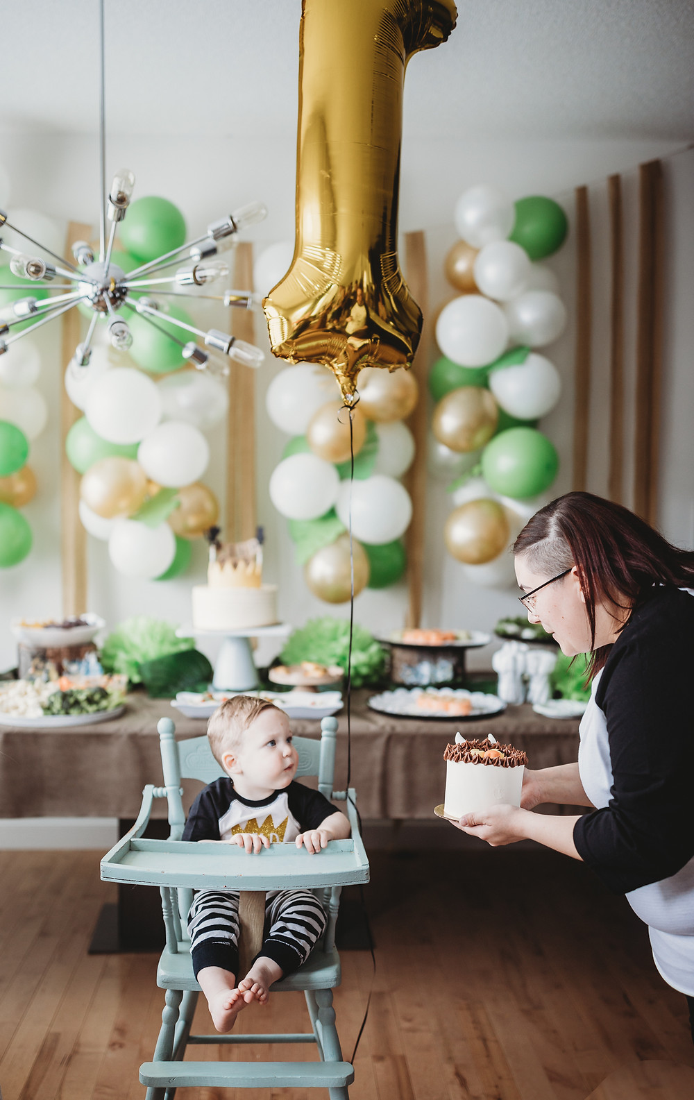 baby first birthday in high chair with mom bringing a cake