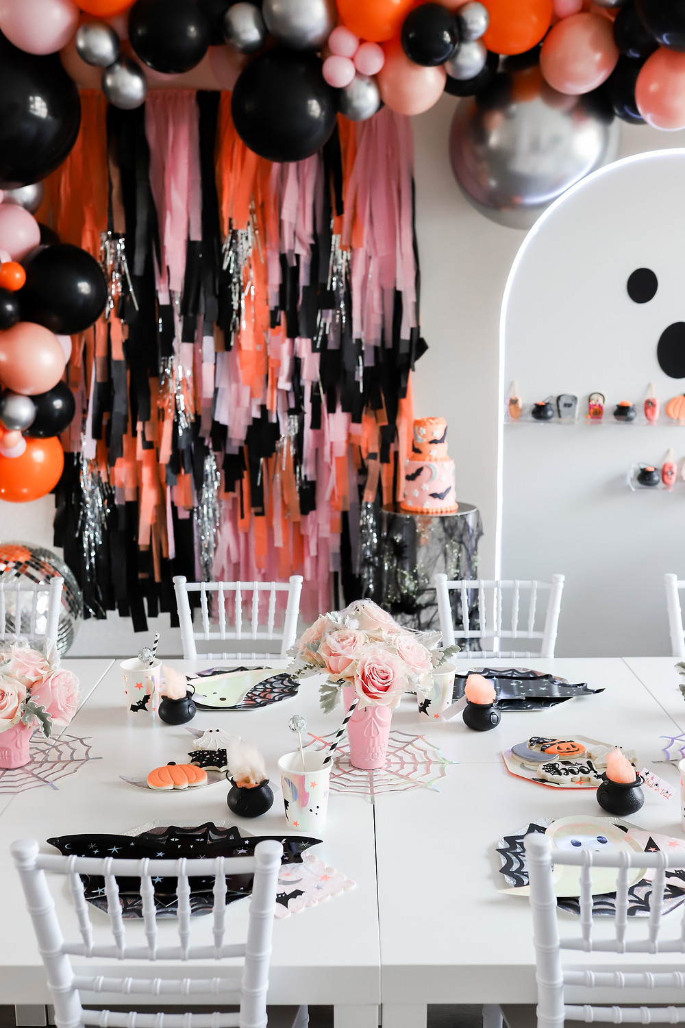 A pink, orange and black halloween themed party with a large balloon arch hanging next to a streamer wall behind a white children's table with bat themed paper plates, pink skulls, a bat cake and pink roses.