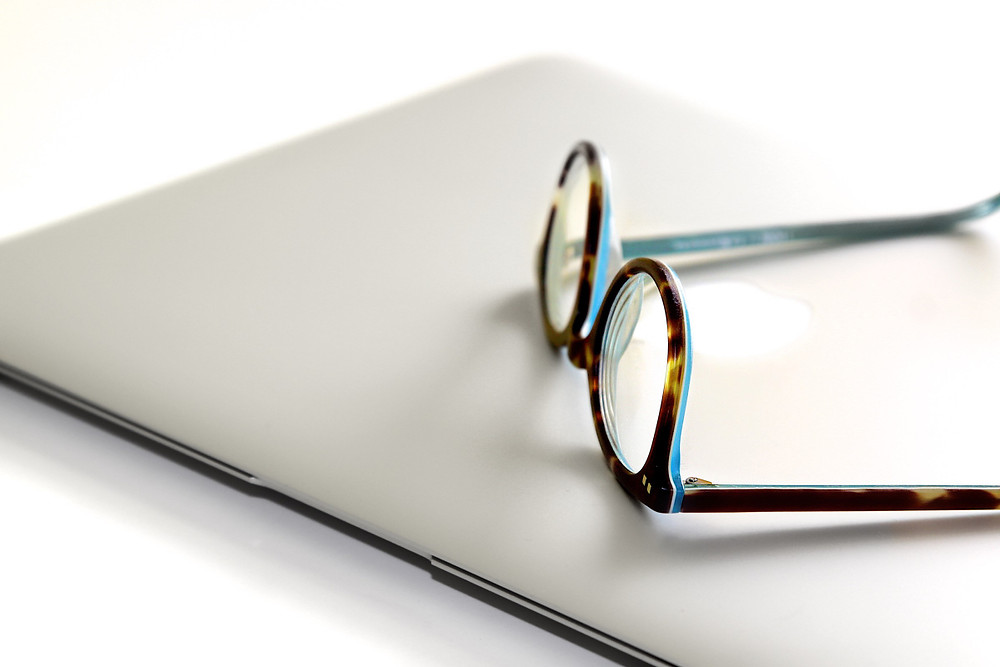Glasses laying on a computer.