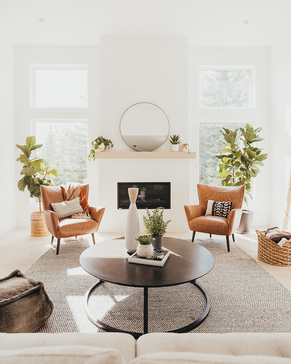 A white Scandinavian living room features light wood floors with a wool rug, light grey sofa, brown fur pouf, two brown leather chairs with pillows, two fiddle leaf fig plants in front of large windows, a metal round coffee table, a wicker basket holding a throw, and a linear white fireplace with a light wood mantel holding a round mirror and some plants.