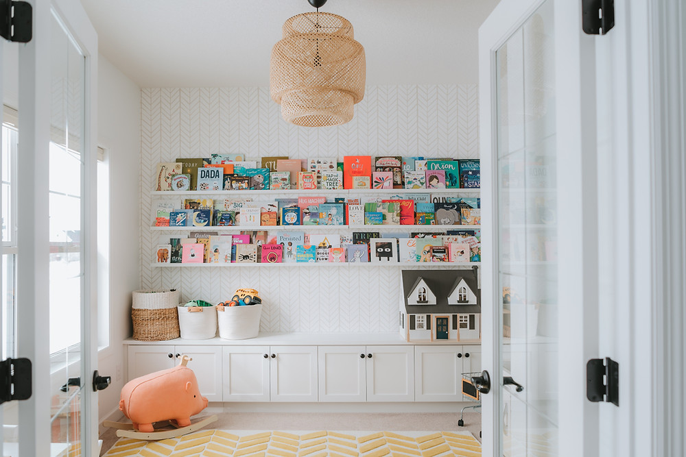 a yellow and white chevron area rug with boho lamp in a kids playroom with long bookshelves lining the walls full of colourful books above white built in shelves.