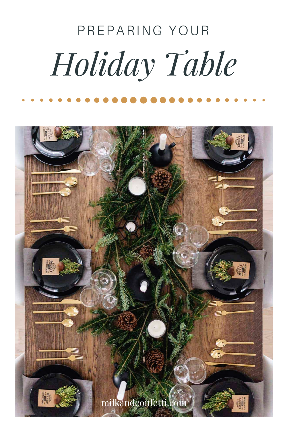 A festive holiday Christmas tablescape with a modern feel decorated with greenery garland, white candles and pine cones amongst black plates and gold cutlery on a brown wooden table.