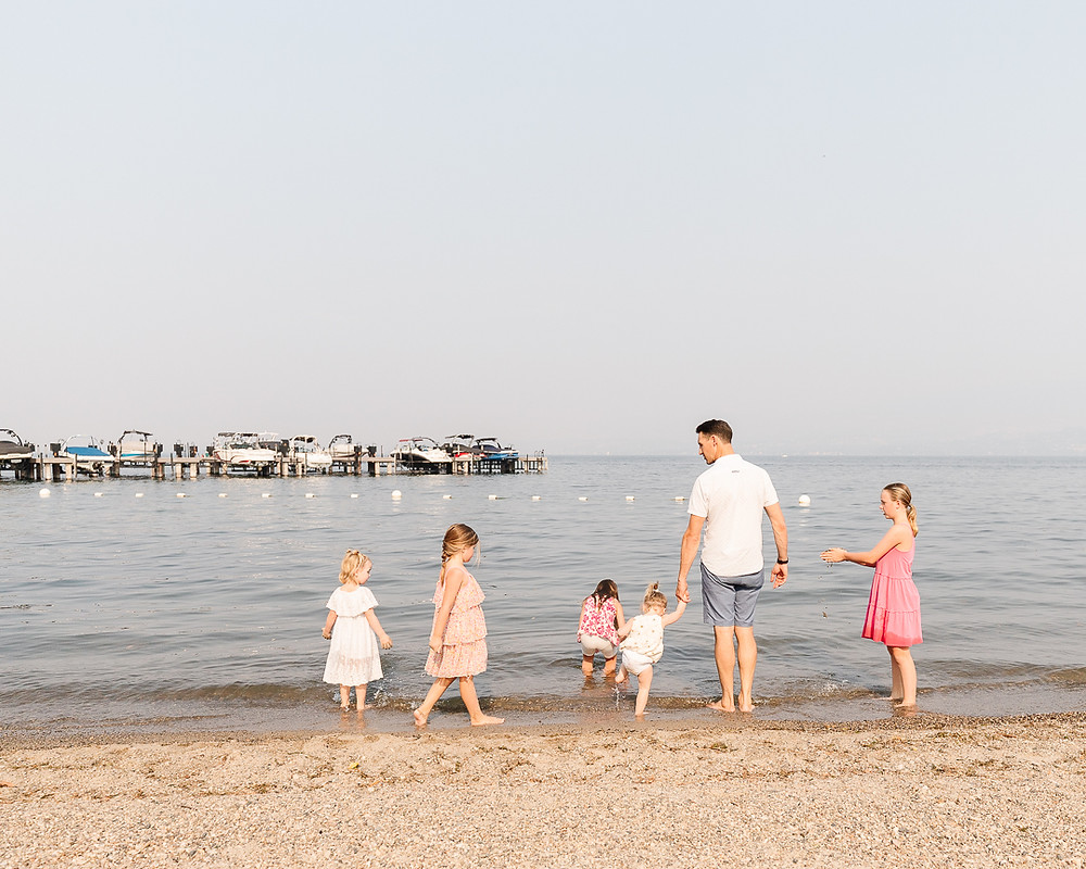 A family on the beach looking at the water with 5 little girls playing in the sand.