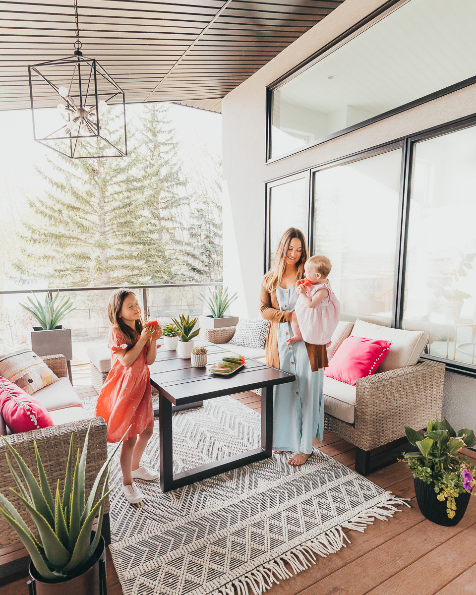 A mom and her two daughters hanging out on a covered deck next to a table and two sofas with a white boho rug,.