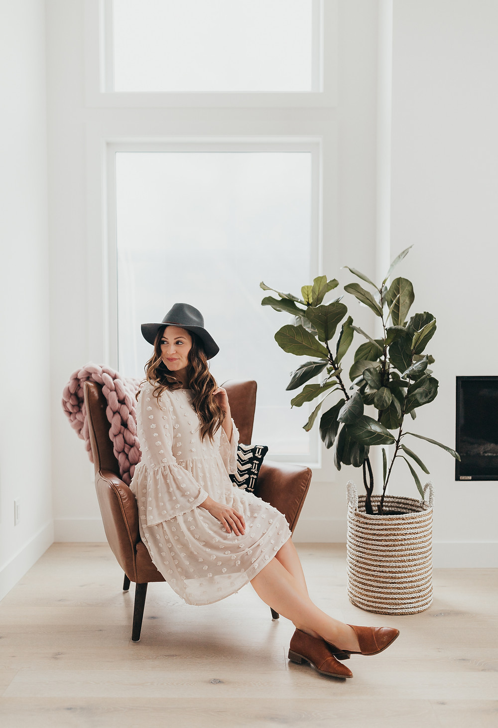 A girl is sitting on a brown leather chair wearing a boho inspired dress
