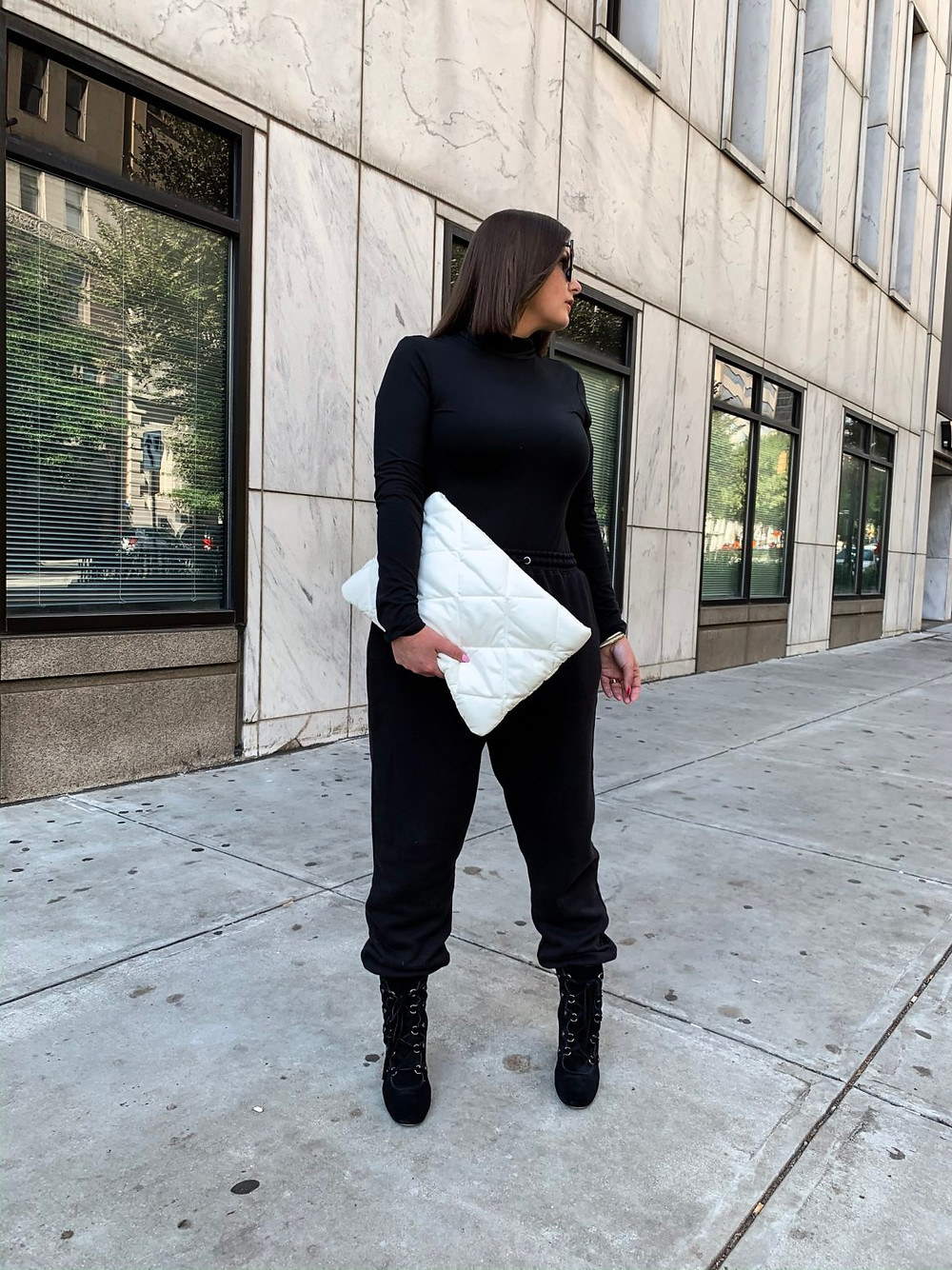 A girl with brunette bob standing on concrete sidewalk wearing a black sweatsuit with black boots while holding a white quilted clutch bag