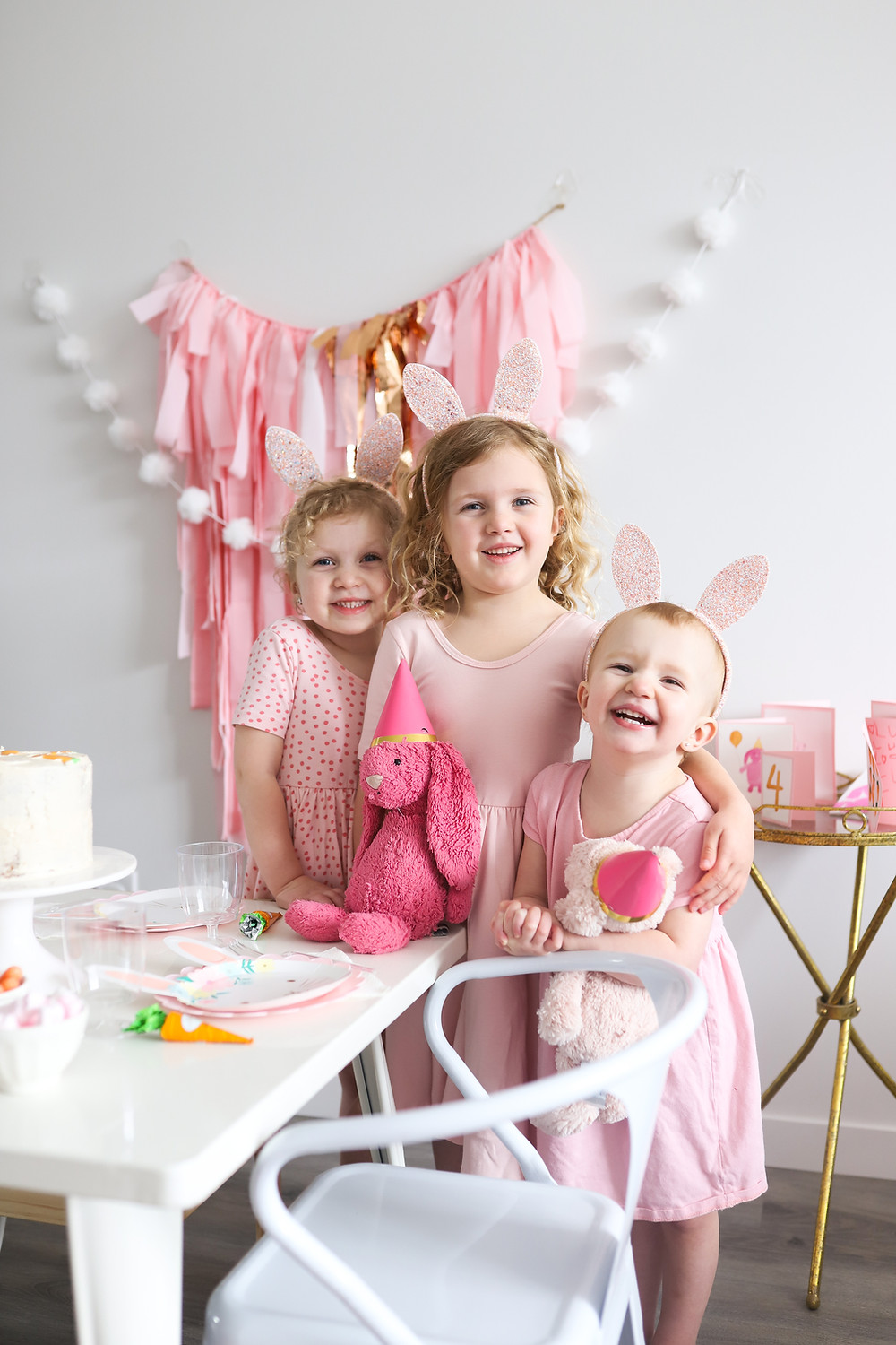 Three little girls smiling at the camera beside a white table decorated for a birthday party.