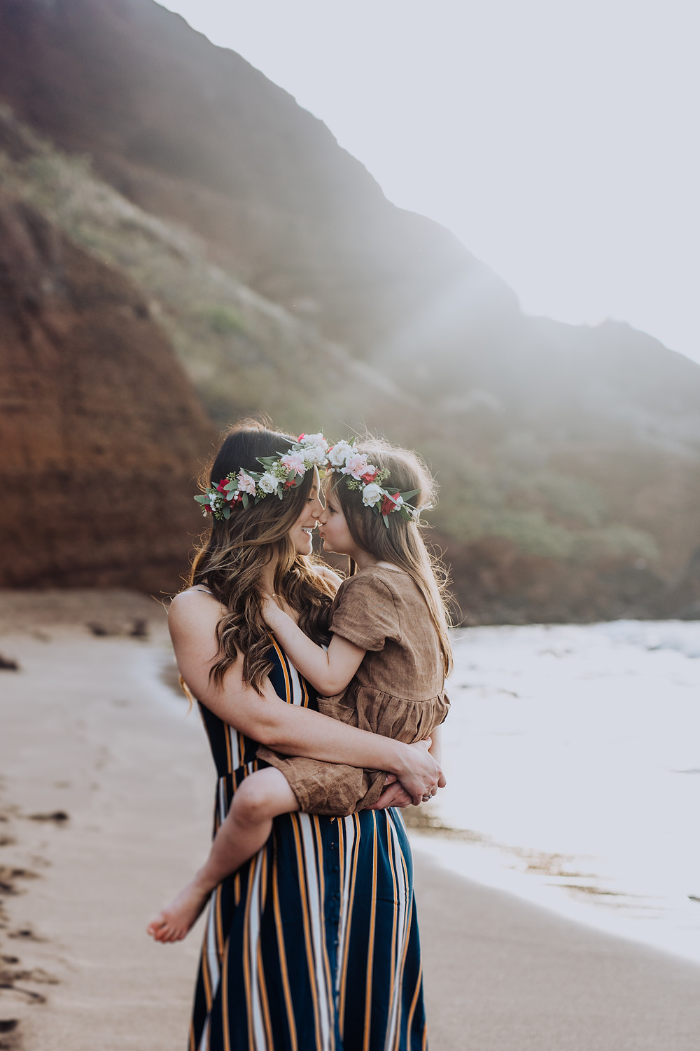 A mother holds her daughter as they kiss each other on the beach.