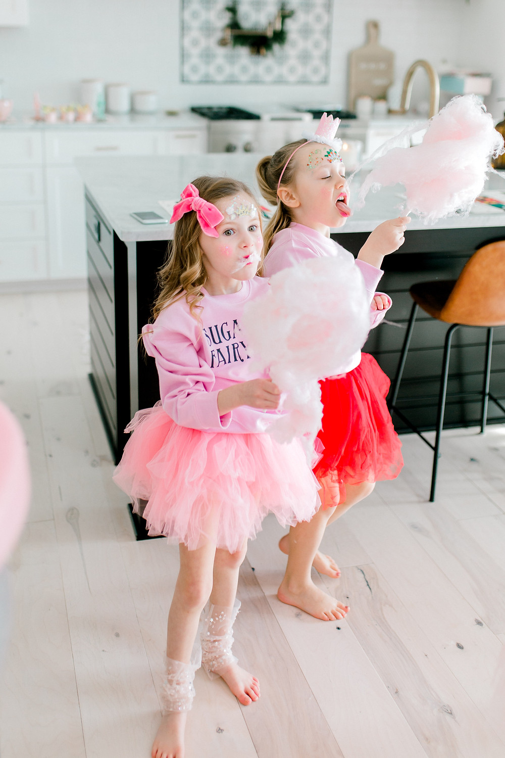 Sugarplum fairies in their pink and red tutus eating pink cotton candy.