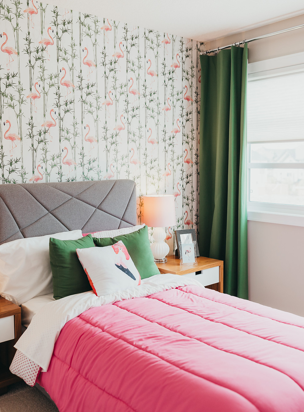 A bedroom decorated with pink and green flamingo wallpaper and pink bedding.