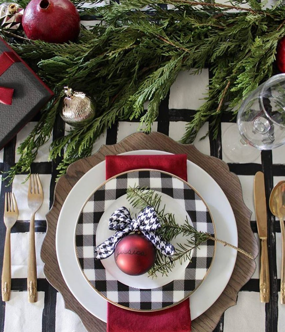 A white and black plaid plate on a plaid table cloth set up for the Christmas holidays on a modern and elegant table next to some greenery and ornaments.