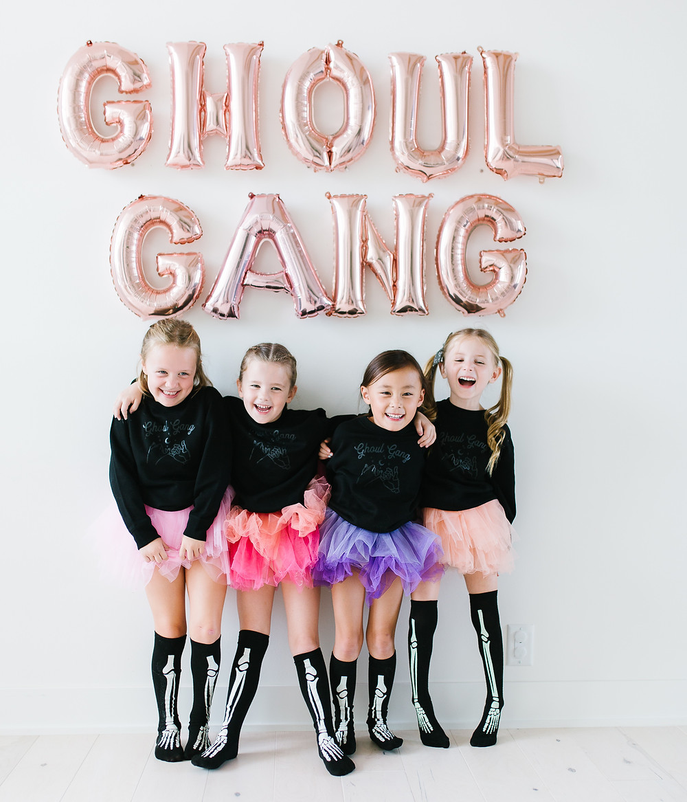 A group of girls at a kids halloween party in tutu's and skeleton socks beneath ghoul gang balloons.