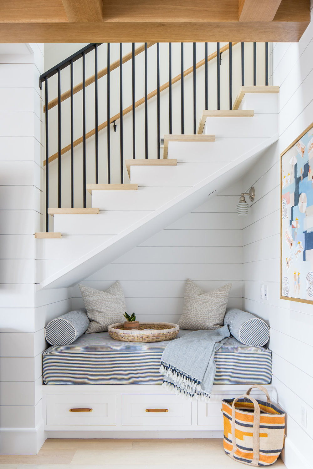 reading nook under stair way with three drawers grey foam mattress with throw pillow and blanket white shiplap detail stairs with wood treads black metal railing and hand rail woven basket abstract painting