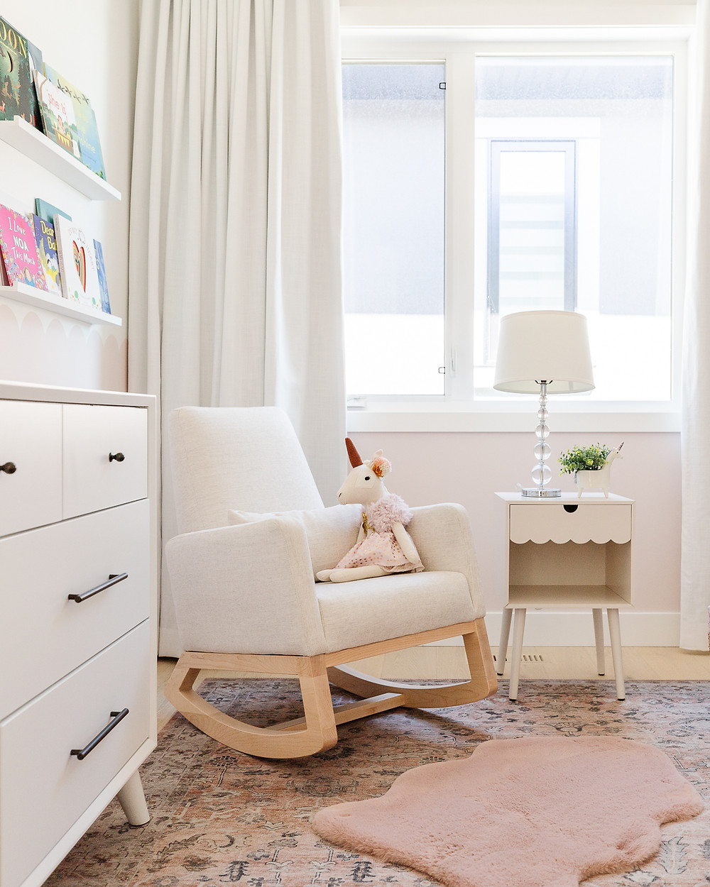 A boho modern baby girls nursery with a blush pink rug a white monte designs joya rocking chair and a scalloped pink wall behind white drapery.