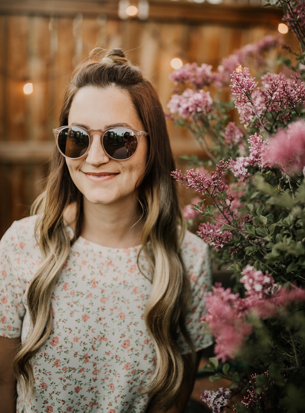 Vintage round sunglasses on girl beside lilac bush