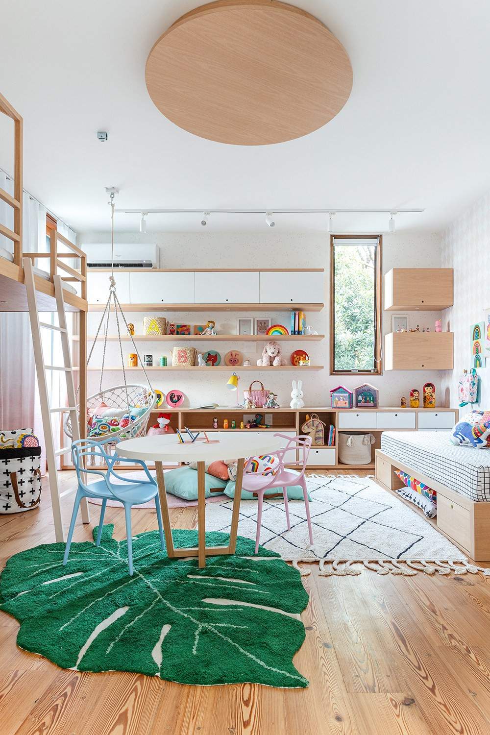 A modern scandinavian neutral childrens rooms with white walls, simple shelving and storage, a bunk bed with white craft table and green leaf area rug as well as white diamond floor rug