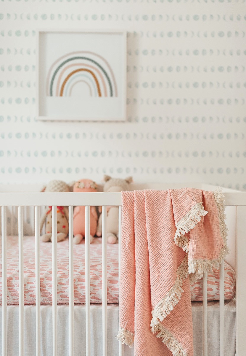 A coral baby blanket hanging over a white crib.
