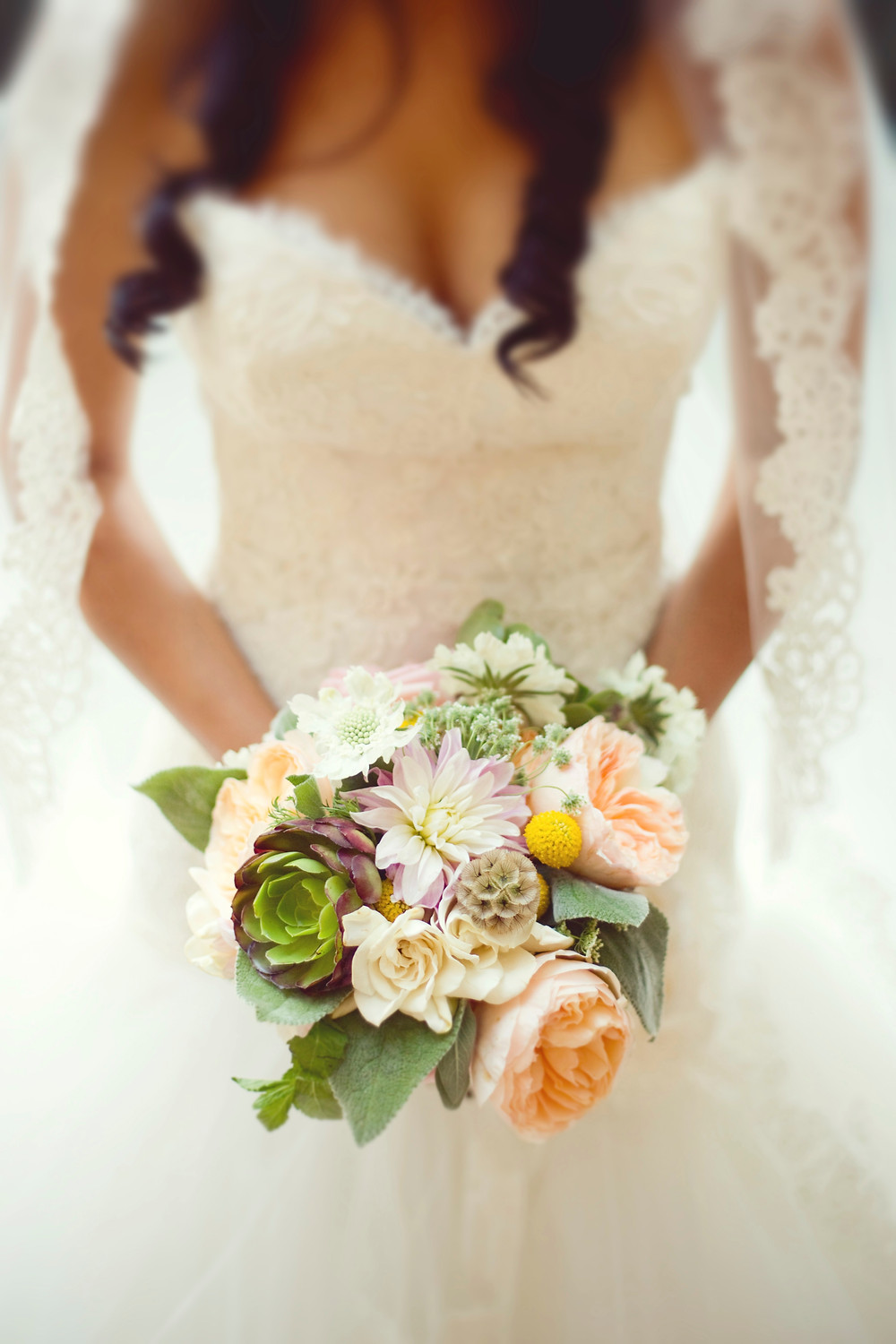 A bride wearing a lace and tulle Lazaro wedding dress is holding a bouquet of garden flowers on her wedding day.