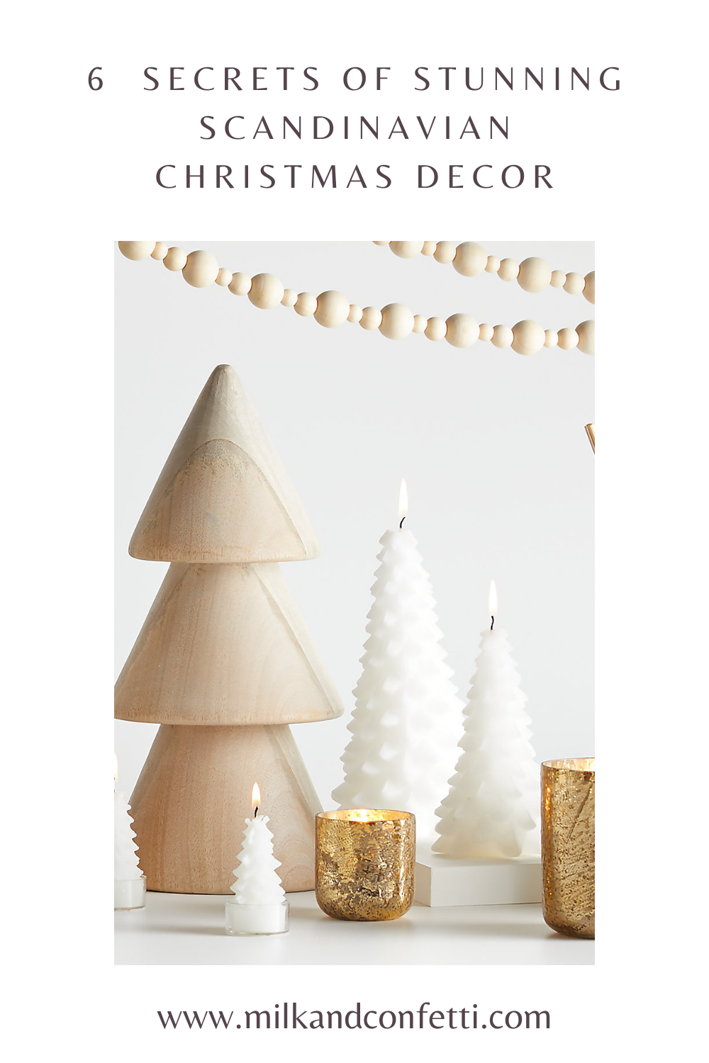 A wooden tree ornament sits beside gold metallic candle holders and white Christmas tree candles under strings of wooden bead garlands for a Scandinavian Christmas display.