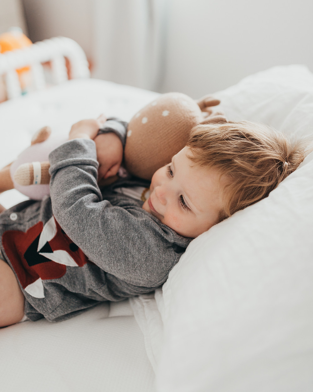 A little boy laying on the bed holding a stuffed animal.
