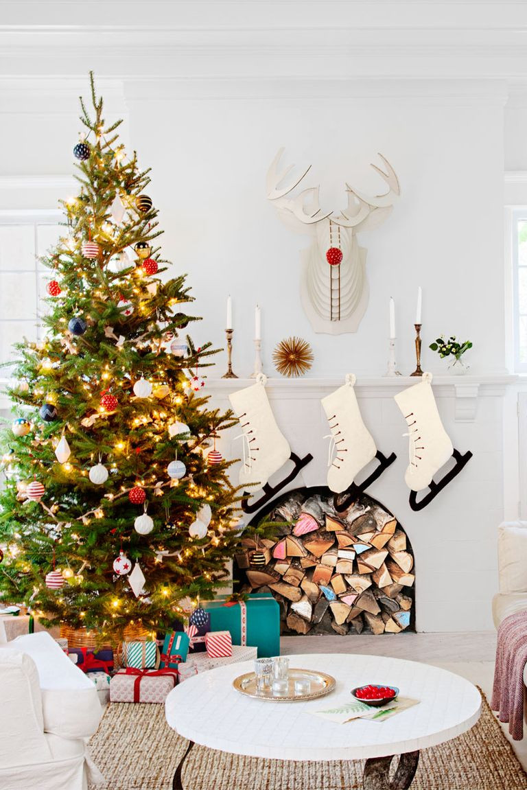 A white Christmas holiday fireplace with a mantel decorated with greenery, stockings and a reindeer head with a stack of coloured gifts below for a modern and cozy feel.