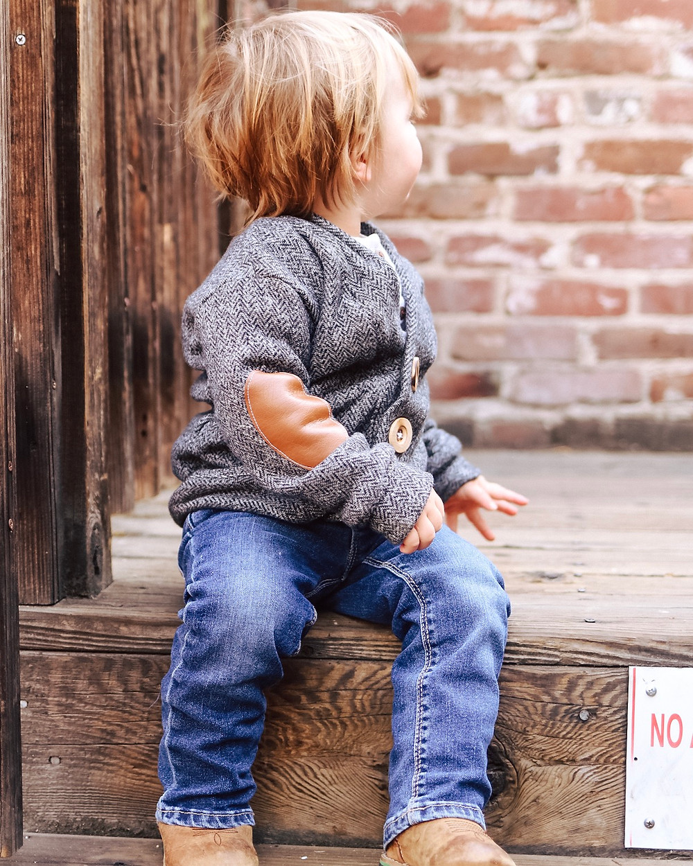 A little boy wearing a sweater with leather elbow patches sitting on a wooden step.