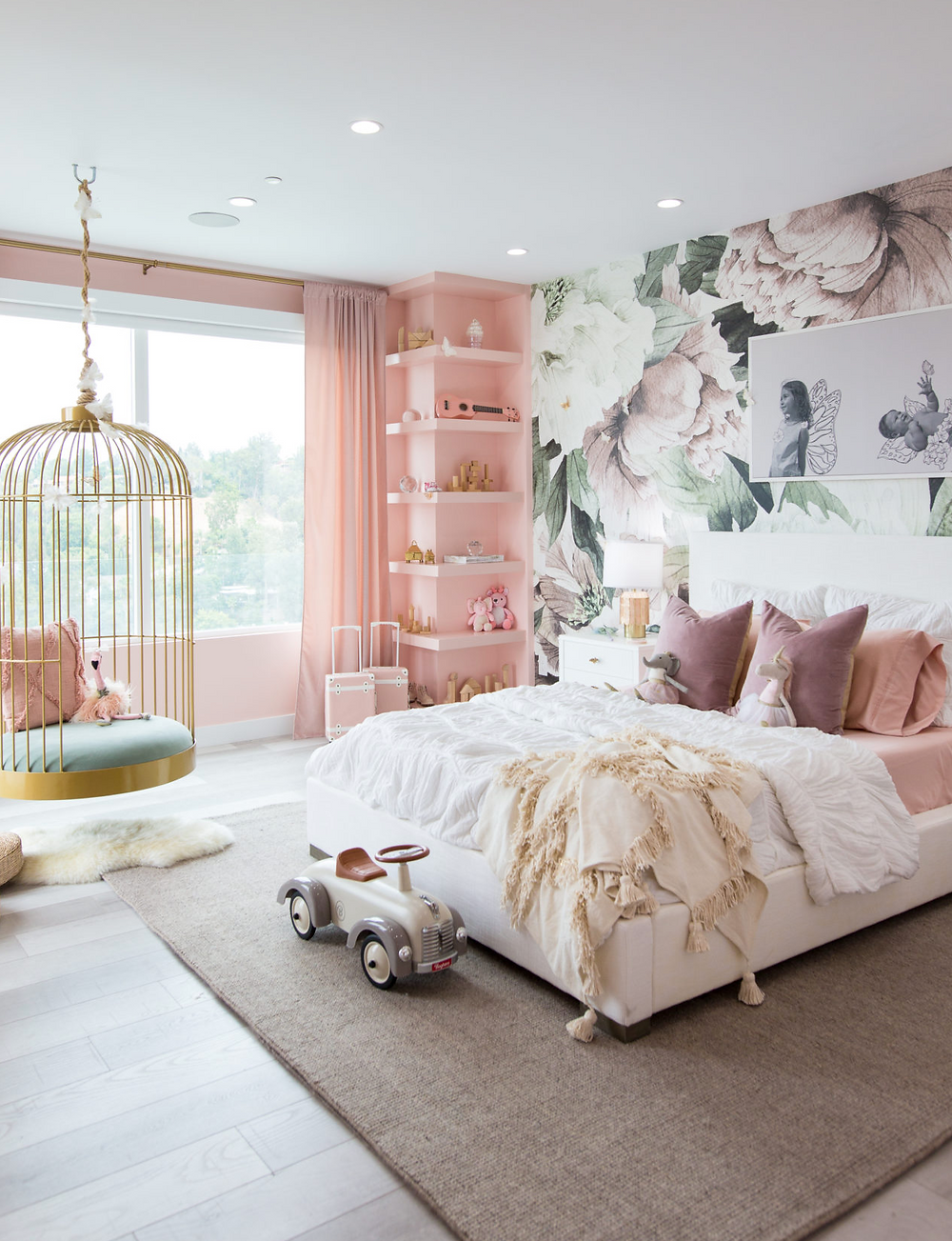 A little girls bedroom with floral wallpaper, pink shelves, a hanging swing and a a large cozy bed.