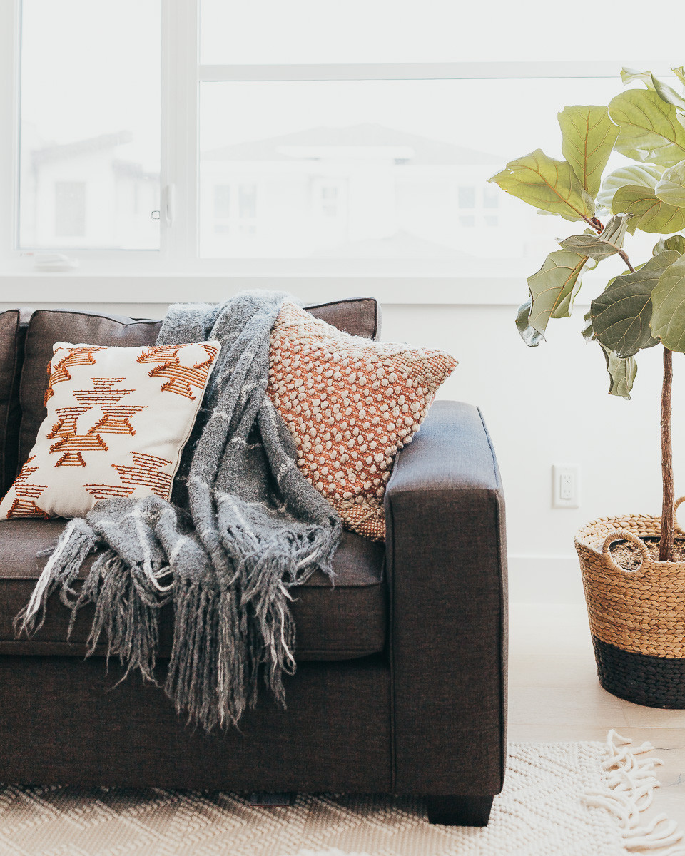 A grey throw blanket laying across a sofa amongst pillows.