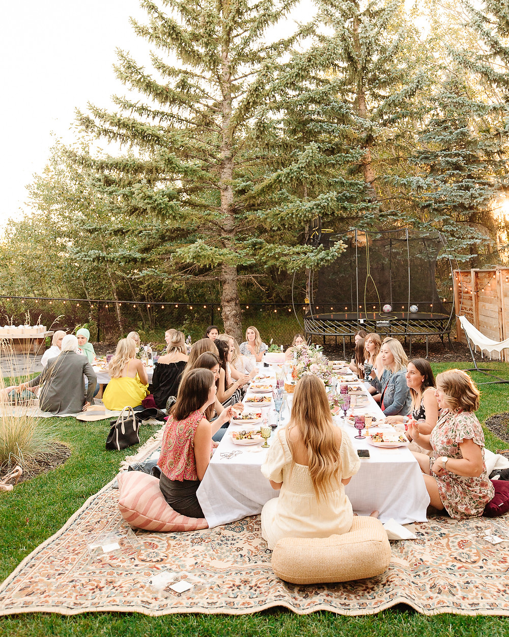 A backyard boho garden party with flowers, vintage rugs, charcuterie wine, twinkle lights, and all your best girlfriends.