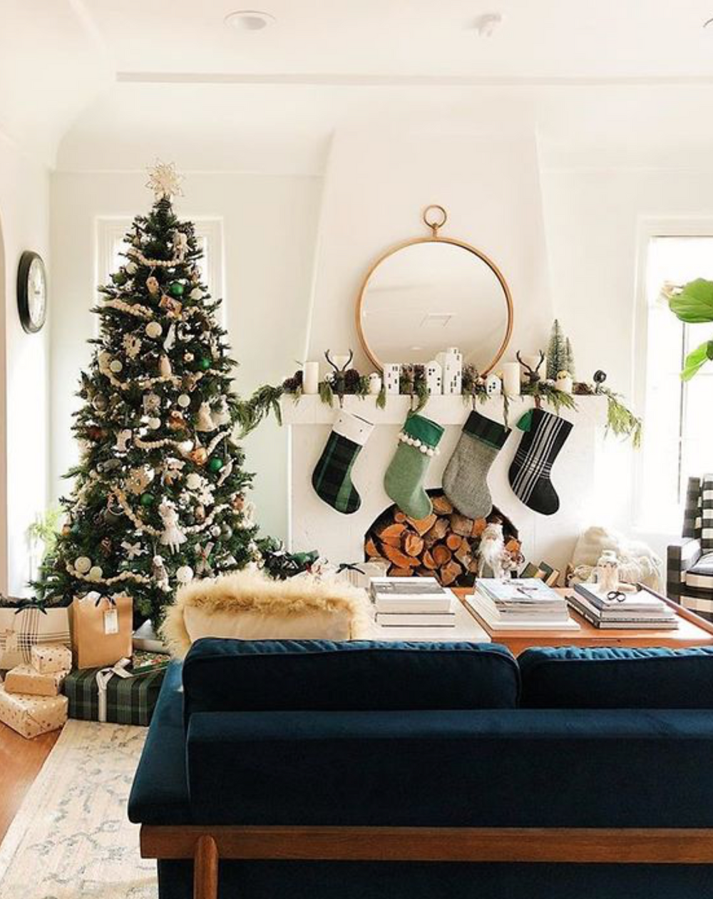 A white Christmas holiday fireplace with a mantel decorated with greenery, a gold mirror and green stockings for a stylish and cozy feel.