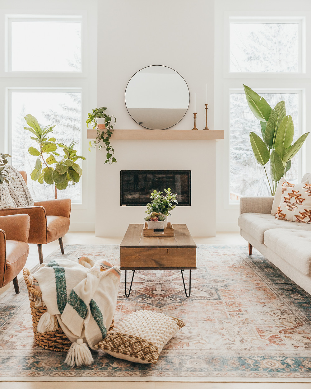 Natural light and two windows on each side of fireplace wood mantle with black circle mirror two candlesticks plant bird of paradise fiddle leaf fig plant rust arm chairs area rug wood and black accent coffee table cream color sofa with aztec pattern throw pillow basket on floor with throw blanket and pillow