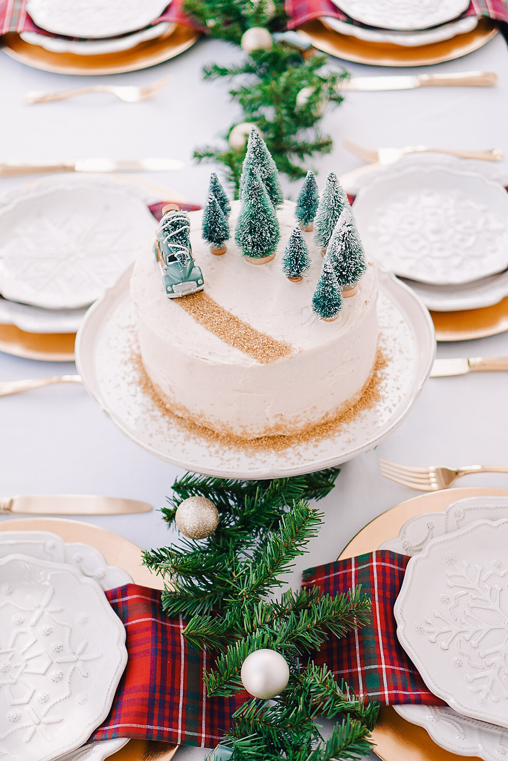 A fun and festive Christmas holiday tablescape with red and green plaid napkins, greenery and bottlebrush trees on a white table.