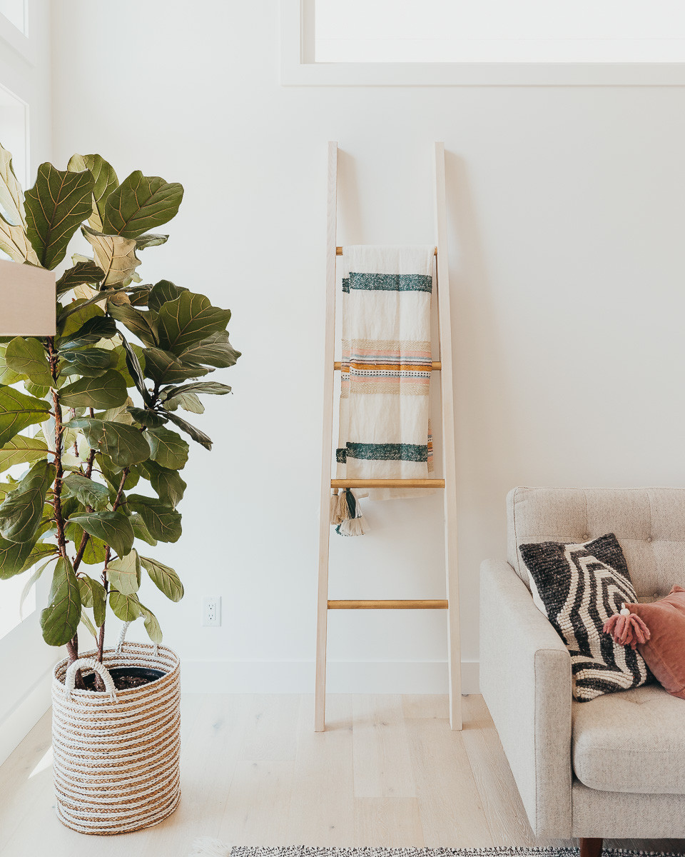 A gold and white blanket ladder standing in a modern living room next to a sofa.